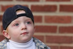 Cute kid looking up. Cute young boy against a brick wall looking up Royalty Free Stock Photo