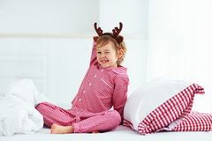 Cute kid making funny faces on winter morning with reindeer antlers, christmas holidays Stock Photo