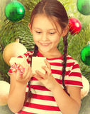 Cute kid opens a box with a gift Royalty Free Stock Photography