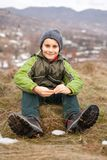 Cute kid outdoor. Cute boy sitting in grass in a countryside environment Stock Images