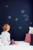 Cute kid in pajamas dreaming , while sitting in bed and looking on chalkboard wall Stock Photography