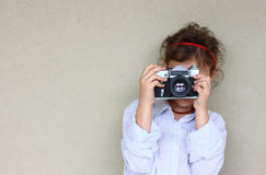 Cute kid photographer holding vintage camera during playing activity. inspiration concept. Stock Photography
