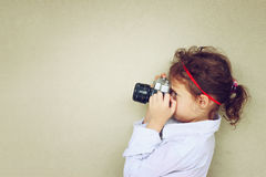 Cute kid photographer holding vintage camera during playing activity. inspiration concept Royalty Free Stock Photo
