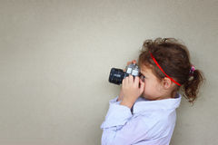 Cute kid photographer holding vintage camera during playing activity. inspiration concept. Royalty Free Stock Photos