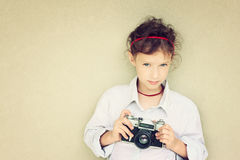 Cute kid photographer holding vintage camera during playing activity. inspiration concept Royalty Free Stock Photography