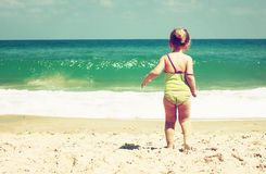 Cute kid playing at the beach. filtered image, retro style. Stock Photo