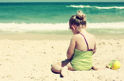 Cute kid playing at the beach. filtered image, retro style. Royalty Free Stock Image