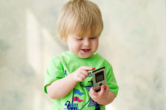 Cute kid playing with cell phone. Portrait of a cute smiling kid typing something on his cell phone Stock Images