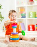 Cute kid playing with color toy indoor Stock Photos