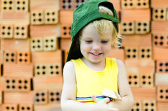Cute kid playing with construction tools on orange bricks backgr Royalty Free Stock Photography