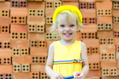 Cute kid playing with construction tools on orange bricks backgr Stock Photography