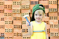 Cute kid playing with construction tools on orange bricks backgr Stock Photos