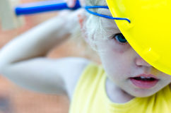 Cute kid playing with construction tools on orange bricks backgr Royalty Free Stock Photo