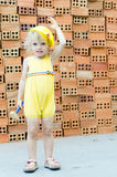 Cute kid playing with construction tools on orange bricks backgr Royalty Free Stock Images
