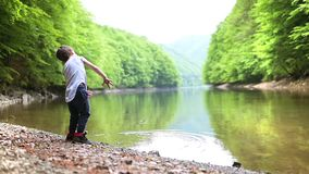 Cute Kid Playing at Lake. Throwing stones in water, summer day stock video