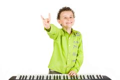Cute kid playing piano. Cute little boy playing synthesizer or piano, isolated on white background Royalty Free Stock Images