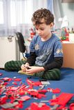 Cute kid playing with plastic blocks Stock Images