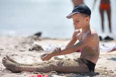 Cute kid playing with sand on the beach Stock Photo