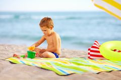 Cute kid playing in sand on the beach royalty free stock photo