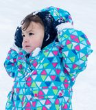 Cute kid playing with snow Stock Photos