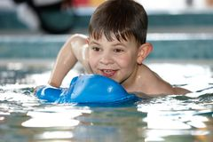 Cute kid playing at swimming pool royalty free stock photos