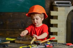 Cute kid playing with tool set. Little carpenter working with wooden block. Small boy in workshop Royalty Free Stock Image