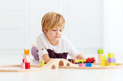 Cute kid playing with toy railway at home Stock Image