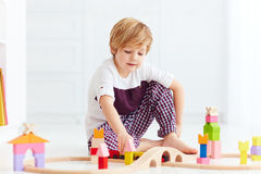 Cute kid playing with toy railway at home Royalty Free Stock Image