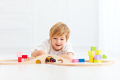 Cute kid playing with toy railway at home Stock Photos