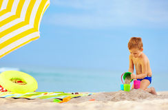 Cute kid playing toys on the beach Stock Images