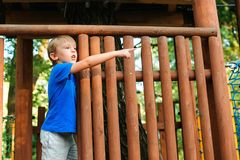 Cute kid playing in tree house on backyard. Happy childhood. Summer holidays concept. Tree house for kids. Happy boy plays in an royalty free stock image