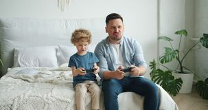 Cute kid playing video game with father holding joysticks having fun in bed. Cute kid is playing video game with happy father holding joysticks having fun in bed stock footage
