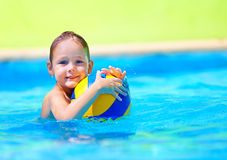 Cute kid playing water sport games in pool. Cute kid, boy playing water sport games in pool Royalty Free Stock Photography