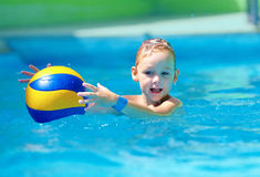 Cute kid playing water sport games in pool. Cute kid, boy playing water sport games in pool royalty free stock photo