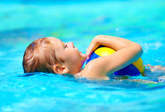 Cute kid playing water sport games in pool Royalty Free Stock Photos