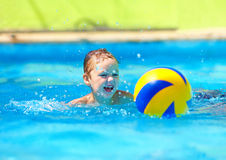 Cute kid playing water sport games in pool Stock Photos
