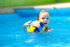 Cute kid playing water sport games in pool Stock Photo