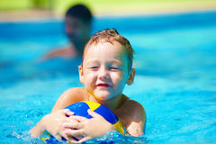Cute kid playing water sport games in pool. Cute kid, boy playing water sport games in pool royalty free stock images