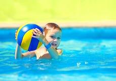 Cute kid playing in water sport games in pool. Cute kid, boy playing water sport games in pool stock image