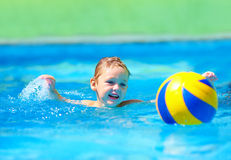 Cute kid playing water sport games in pool. Cute kid, boy playing water sport games in pool royalty free stock photos