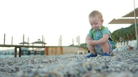 A cute kid plays alone by the sea. He carefully touches and examines the colored stones. Blondin boy less than two years. Old stock footage