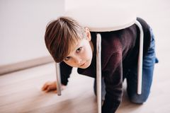 A cute kid plays on the floor pretending a turtle. A cute boy kid plays on the floor with a stool on his back, pretending a turtle, soft focus Stock Image
