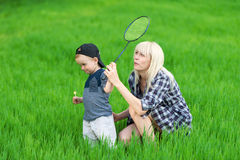 Cute kid plays with mother in tennis outdoors. Stock Photo