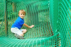 Cute kid plays at outdoors playground. Modern rope adventure park. Happy childhood. Happy summer holidays.  royalty free stock image