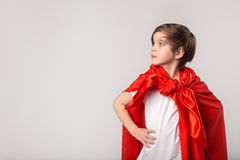 Cute kid pretend superwoman in studio. Cute kid in red cape pretend superwoman in studio royalty free stock photos