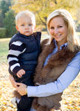 Cute kid and pretty mom outdoors at fall. Royalty Free Stock Photography