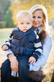 Cute kid and pretty mom outdoors at fall. Stock Images