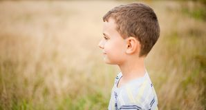 Cute kid profile. Portrait of a cute kid in profile, over a blurred nature background Royalty Free Stock Photos