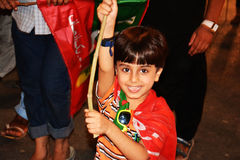 Cute Kid at Raiwind March – 30 September 2016. A cute kid holding PTI Flag and smiling. Pakistan Tehreek E Insaf was running a movement against prime minister Stock Image