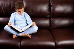 Cute kid reading a big book on a sofa. Cute schoolboy in pajamas reading a book (a dictionary) while sitting on a sofa Stock Photo